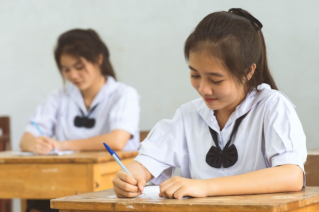 Students writing pen in hand doing exams answer sheets exercises in classroom with not stress. Premium Photo