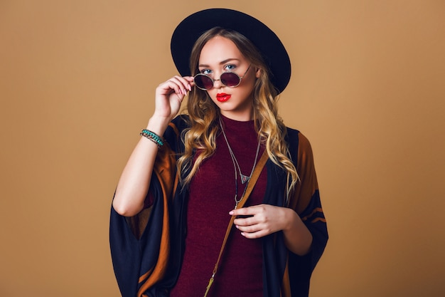 Studio close up portrait of young fresh blonde  woman in brown straw poncho , wool black trendy hat and round glasses looking at camera. green leather had bag. Free Photo