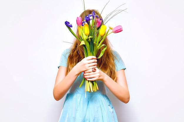 ブロンドの女性のスタジオ面白い肖像画は、色とりどりのチューリップ、柔らかいパステルカラー、ヴィンテージのドレス、長い毛、ファッションの詳細の美しい花束で顔を閉じます。春が来る 無料写真