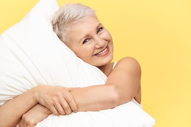 귀여운 매력적인 중간 나이 든된 여성 포옹 흰색 베개, 잠에, 행복 한 쾌활 한 표정을 갖는 스튜디오 이미지. 무료 사진