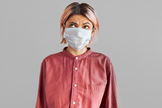 Studio immagine di premurosa giovane donna europea con espressione facciale pensierosa che indossa una maschera progettata per proteggere le persone dall'inalazione di batteri o virus presenti nell'aria. concetto di pandemia di coronavirus Foto Gratuite