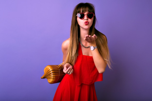 空気のキスをあなたに送る夏のエレガントな赤いドレス、ヘラートサングラス、木製バッグを身に着けているかなりブルネットのトレンディな女性のスタジオライフスタイルの肖像画。 無料写真