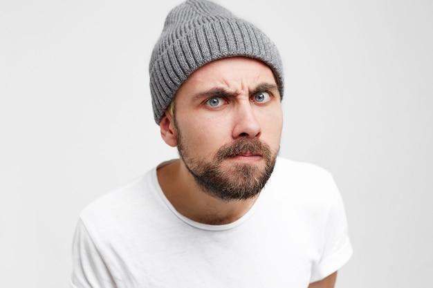 Студийное фото молодого человека, как бы смотрящего в глазок с интересом, пронзительно, придирчиво Бесплатные Фотографии