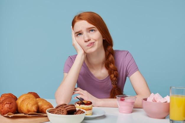 Foto di studio della ragazza dai capelli rossi triste, dubbioso medita pensando a cibo, salute, dieta, calorie extra, prodotti da forno e frutta fresca Foto Gratuite