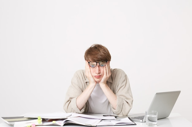 Studio photo of tired student sitting with his elbows on his desk holding his head Free Photo