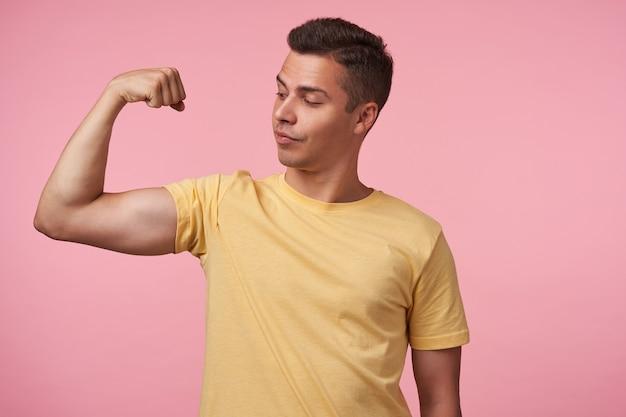 Studio foto del giovane bello dai capelli castani uomo che guarda con orgoglio la sua mano mentre dimostra il suo forte bicipite, in piedi su sfondo rosa in abbigliamento casual Foto Gratuite