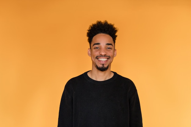 Studio portrait of afro american man wearing black pullover smiling over orange wall. Free Photo