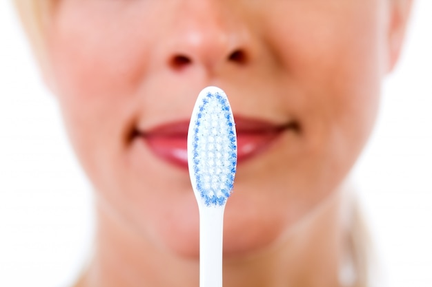 Studio portrait of beautiful young woman posing with toothbrush Free Photo