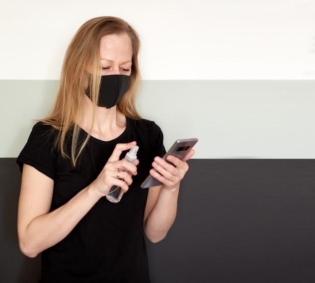 コロナウイルス中にスプレー消毒剤で電話を消毒するフェイスマスクの金髪女性のスタジオポートレート Premium写真