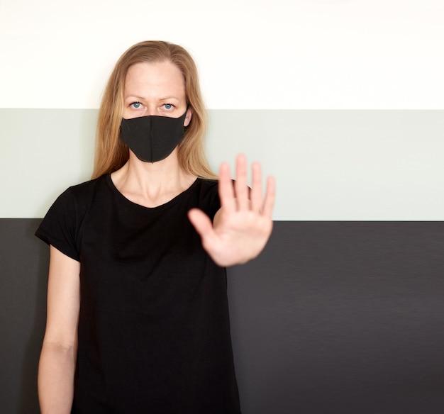 コロナウイルスの流行中に保護するためのフェイスマスクの金髪女性のスタジオポートレート。 Premium写真