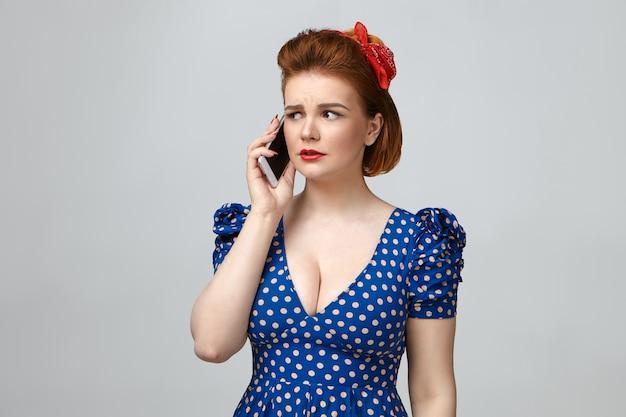明るいメイクと表情を心配しているローカットのレトロな点線のドレスを着ている欲求不満の美しい若い主婦のスタジオポートレート 無料写真