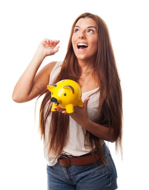 Studio portrait of girl holding yellow moneybox. Free Photo