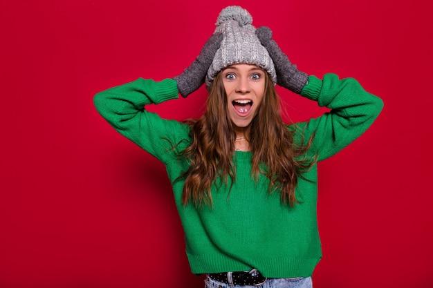 녹색 풀오버와 열린 입으로 카메라에 포즈를 취하는 회색 겨울 모자를 쓰고 긴 밝은 갈색 머리를 가진 사랑스러운 종료 행복한 여자의 스튜디오 초상화와 손, 격리 된 배경을 보유 무료 사진