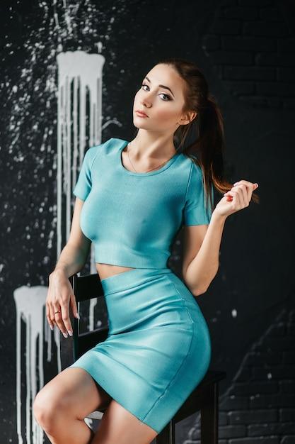 Студийный портрет сексуальная брюнетка с хвостом в синем топе и юбке Premium Фотографии