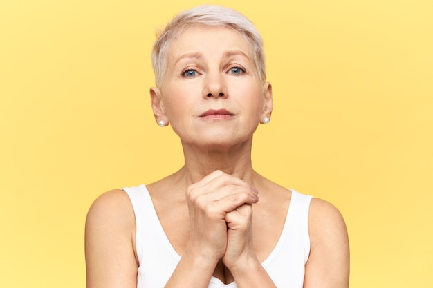 Studio portrait of upset retired caucasian woman having desperate mournful look, keeping hands clasped on chest, praying, her heart filled with faith and belief, waiting for miracle. body language Free Photo