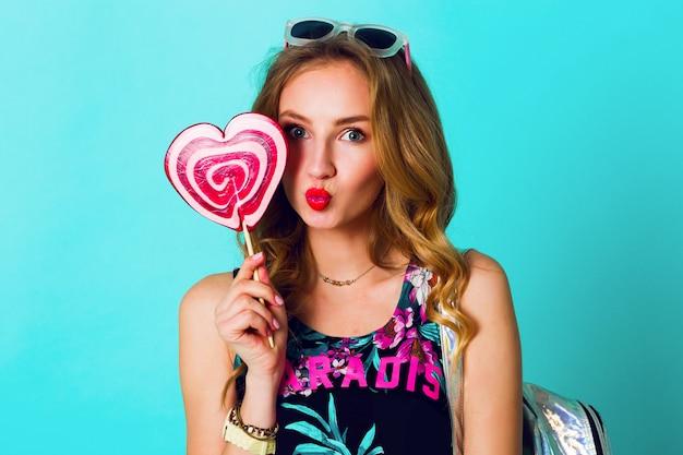 プリントトップ、ネオンバックパック、かわいいメガネを身に着けているピンクのロリポップの夏スタイルの衣装で青い壁の背景にポーズをとって若いセクシーな面白いファッションクレイジー女性のスタジオ肯定的な肖像画。 無料写真