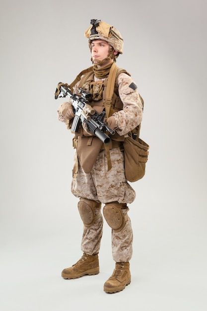 Студийная съемка современного пехотинца, американского морского стрелка в боевой форме, шлеме и бронежилете Premium Фотографии