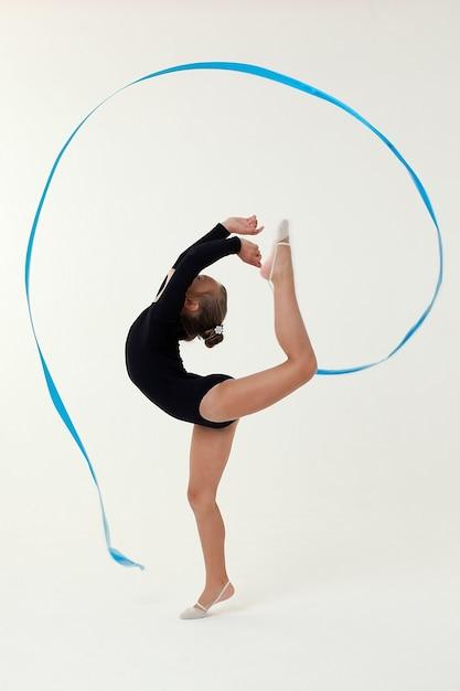 Студийная съемка маленькой гимнастки на светлом пространстве Premium Фотографии