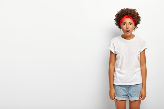 Studio shot di stupito hipster ragazza guarda la telecamera con la bocca aperta Foto Gratuite