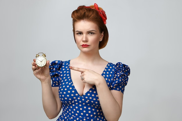 Studio shot of angry beautiful young woman dressed in vintage clothes looking at camera with annoyed expression, pointing index finger at alarm clock in her hand, meaning: you are late again Free Photo