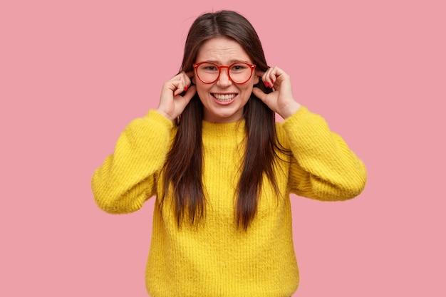 Studio shot di donna infastidita tappi le orecchie con le dita, esprime negatività, stringe i denti, indossa casual abiti gialli Foto Gratuite