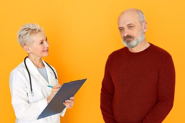 Studio shot di attraente fiducioso donna di mezza età medico con uno stetoscopio intorno al collo tenendo appunti, grafia sintomi durante il trattamento di triste usnhaven uomo anziano, ordinazione di analisi del sangue Foto Gratuite
