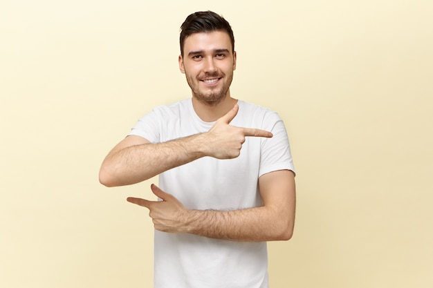 Studio shot of attractive young dark haired man in white t-shirt looking at camera with broad smile, pointing fore fingers at opposite directions, trying to confuse you, showing way Free Photo