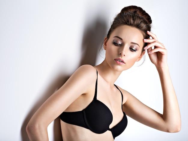 Studio shot di una bella e sexy ragazza con i capelli lunghi che indossa reggiseno nero Foto Gratuite