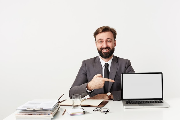 Studio shot of brunette bearded guy with short haircut posing over white wall in formal clothes, showing on his laptop with raised hand and looking cheerfully at front Free Photo