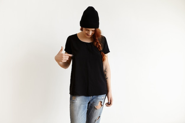 Studio shot of caucasian girl in stylish hat and ragged blue jeans, looking down and pointing index finger Free Photo