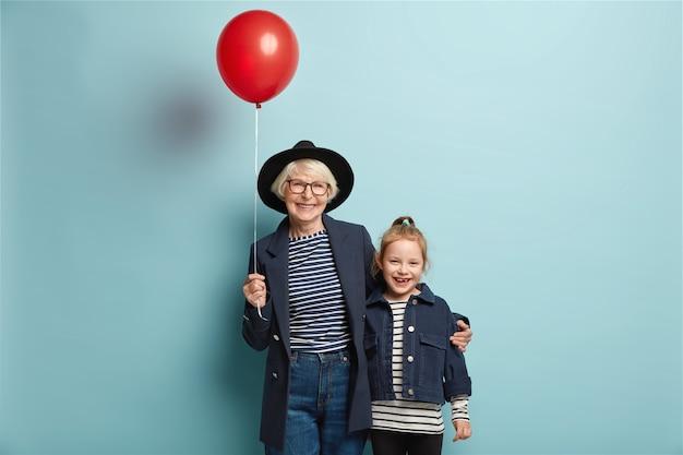 Studio shot di allegro nipote e nonna abbracciare insieme, vieni alla festa Foto Gratuite