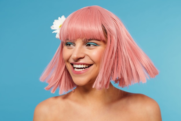 Studio shot of cheerful young beautiful woman wearing white flower in her short pink hair while posing over blue background, laughing happily while looking aside Free Photo