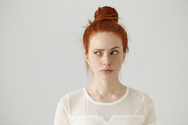 Studio shot of cute redhead girl with hair knot and freckles looking sideways Free Photo