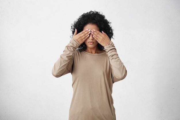 Studio shot di giovane femmina dalla carnagione scura con capelli ricci neri che coprono gli occhi Foto Gratuite