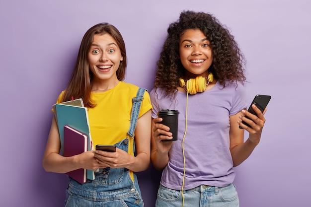 Studio shot di amiche in posa con i loro telefoni Foto Gratuite