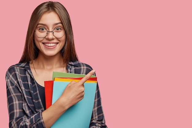 Studio shot of good looking young businesswoman posing against the pink wall with glasses Free Photo