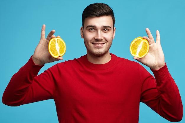 Lo studio ha sparato del vegetariano maschio europeo giovane positivo bello in maglione rosso che posa alla parete blu Foto Gratuite