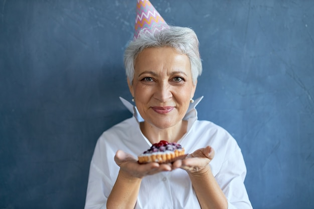 Studio shot di felice beauitful femmina di mezza età che indossa un cappello conico per celebrare il compleanno, posa isolata con la torta nelle sue mani, offrendoti di avere un morso. messa a fuoco selettiva sul volto di donna Foto Gratuite