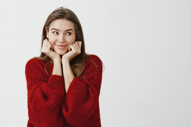 Studio shot of happy cute caucasian female coworker in stylish loose sweater, leaning on hands and looking aside with curious cheerful smile, being in good mood, waiting for her order in restaurant Free Photo