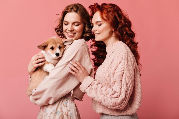 Studio shot di ragazze felici che giocano con il simpatico cane. ridere le signore caucasiche in posa con animali su sfondo rosa. Foto Gratuite