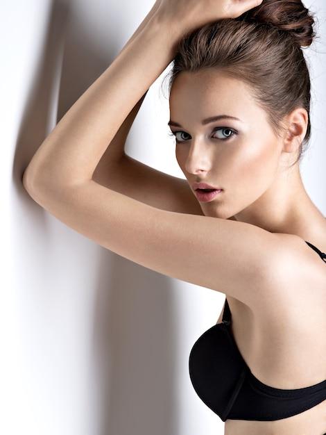 黒のブラジャーを身に着けている長い髪の美しくセクシーな女の子のスタジオショット 無料写真