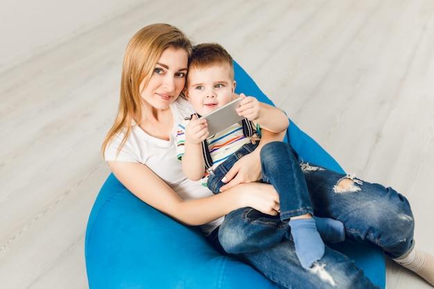 腕の中で彼女の子供を持つお母さんのスタジオ撮影。少年はスマートフォンで遊んで笑顔 無料写真