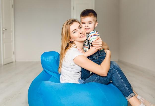 彼女の子供を持つお母さんのスタジオ撮影。ママは男の子を抱擁します。 無料写真