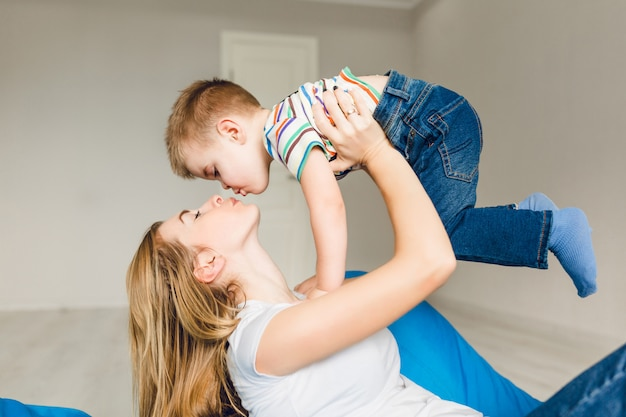 彼女の子供と遊ぶ母のスタジオ撮影。ママは彼女の腕の中で少年を保持しています。 無料写真