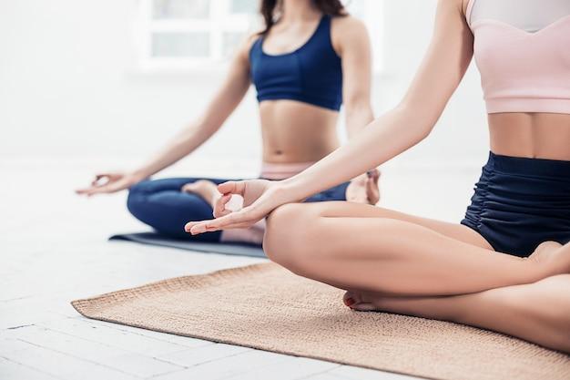 Студийный снимок молодых женщин, делающих упражнения йоги на белом Бесплатные Фотографии