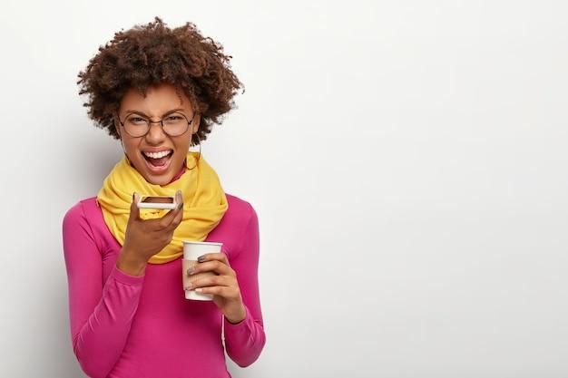 아프로 헤어 스타일로 화가 난 초조 한 여자의 스튜디오 샷, 스마트 폰을 통해 음성 통화를하고, 테이크 아웃 커피를 마시고, 광학 안경, 핑크 터틀넥과 노란색 스카프를 착용하고, 흰 벽 위에 절연 무료 사진