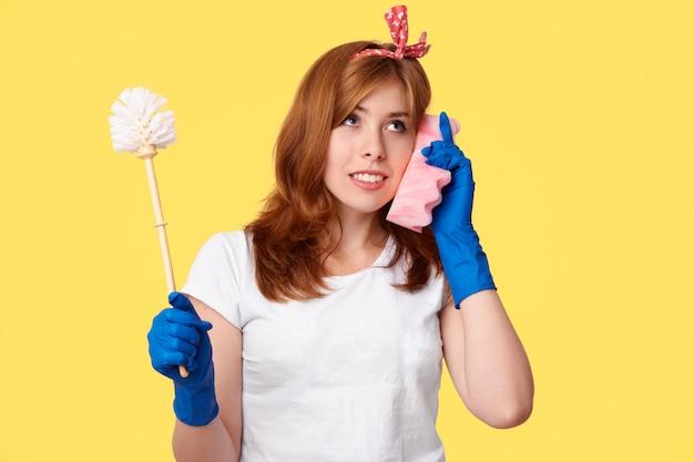 丁寧なメイドのスタジオショットは、ブラシを保持し、携帯電話としてスポンジを使用し、カジュアルな服を着て、黄色のポーズで友人と何かを話し合います。洗浄と衛生の概念 無料写真