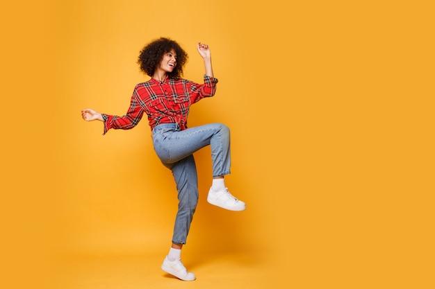 明るいオレンジ色の背景に幸せそうな表情でジャンプする黒の女の子のスタジオ撮影。ジーンズ、白いスニーカー、赤いシャツを着ています。 無料写真