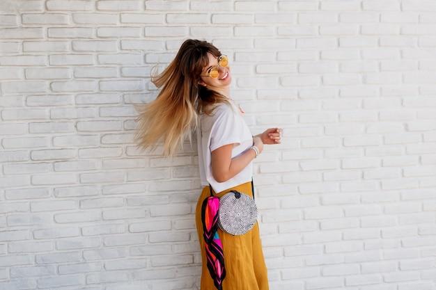 Студийный снимок беззаботной женщины в ярком летнем наряде, позирующей над белой кирпичной стеной Бесплатные Фотографии
