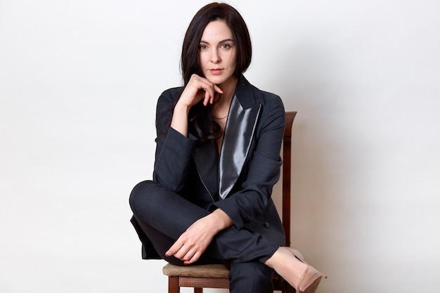 Съемка студии уверенно женщины брюнет сидя на деревянном стуле и держа кулак под подбородком Бесплатные Фотографии